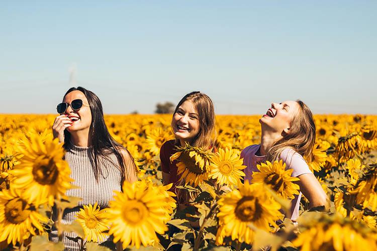 jeunes femmes pleines de ressources qui montrent une véritable joie de vivre au milieu d'un champ de tournesols