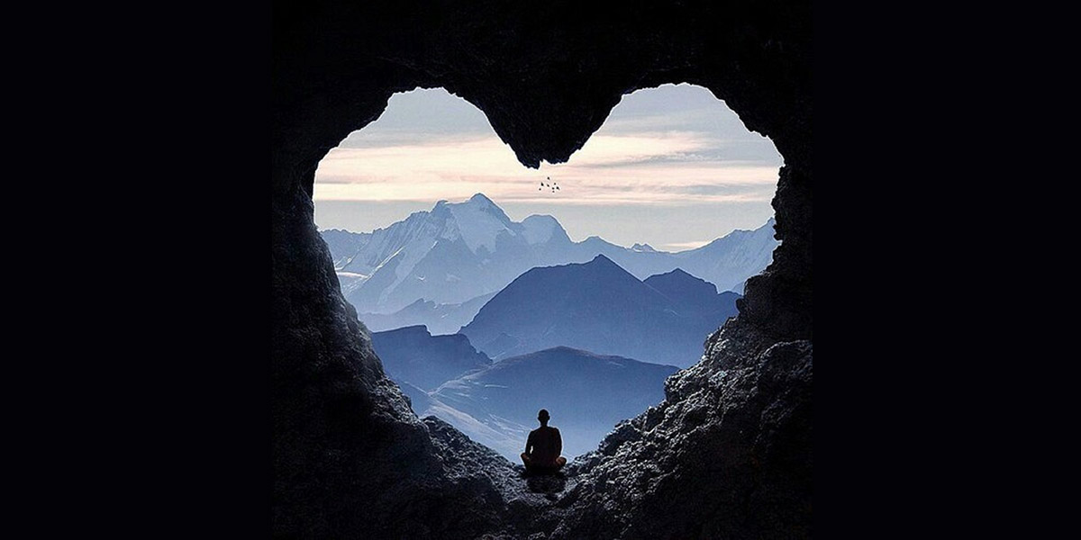 une personne seule au centre d'un coeur dans la pénombre . Cette personne regarde vers l'horizon