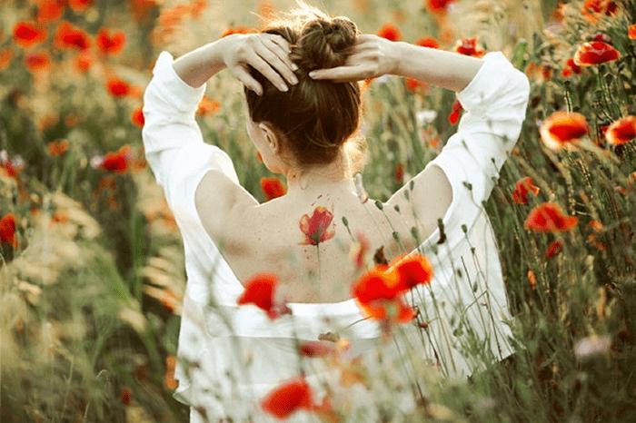 une jeune femme dans un champs de coquelicots en harmonie avec elle-même et pleines de ressources